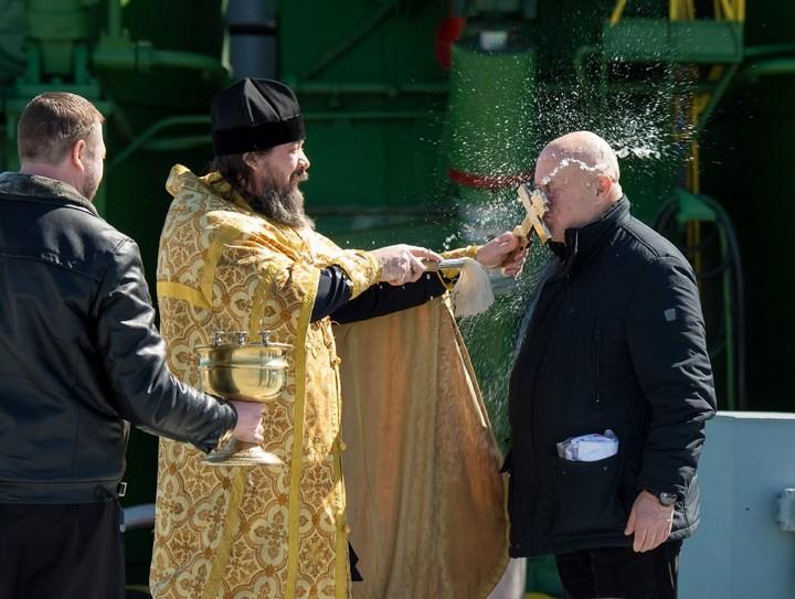 Православный священник благословляет Сергея Семченко возле ракеты «Союз»